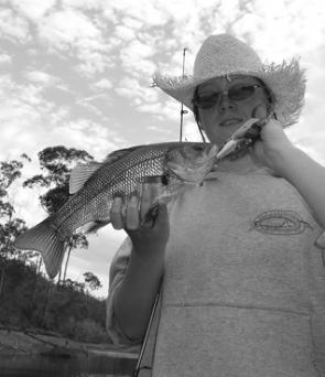 The author's daughter with a Brogo Dam bass. Look for those lovely balmy nights when the insect life is very active and surface fishing is at its best.