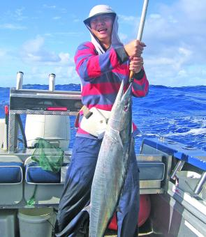 A very satisfied customer, Alvin Lim, with a wahoo he caught on charter with the author.