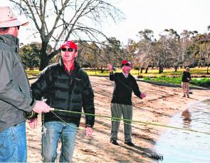 Peter Hayes in red cap, teaching a fly class on the shores of Lake Ginninderra.