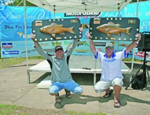 Winners are grinners – Stephen Kanowski (left) holding up his BASS Pro 2007 Angler of the Year trophy next to Kerry Symes (right) holding his BASS Pro 2007 Grand Final Champion trophy.