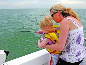 Mia battles her first fish - with some help from mum.