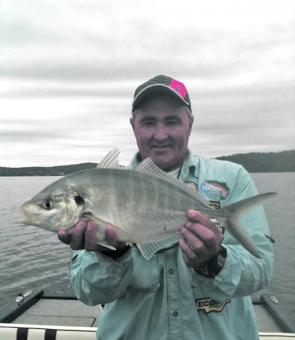 The author with a silver trevally caught on a vibe lure.