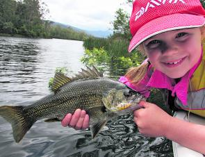 The author's daughter picked up this Brogo brawler by trolling a lure past a fallen wattle tree, (in back ground) Trolling the edges is a good way to get the kids connected to a Brogo Bass.
