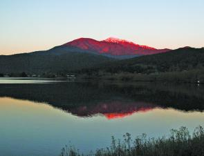 A snow capped Mt Bogong towers over the Mt Beauty pondage at sunset in Mt Beauty.