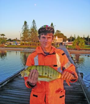 Aaron with a golden trevally taken at Military Jetty.