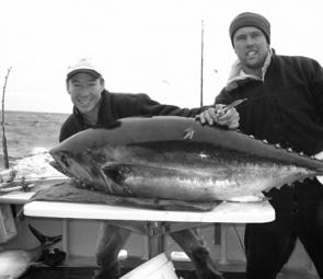 Cam McCallum and Scott Gray pose for the camera with a bluefin tuna as another rod goes off in the background.