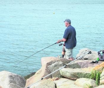 This angler has his long handle net at the ready while patiently watching for his float to go down.