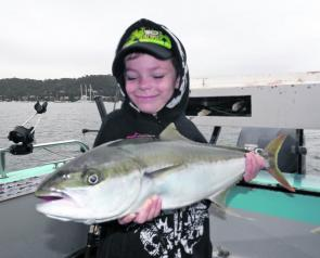 Bailey proudly displays the kingfish he helped his dad to catch.