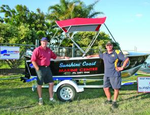Paul Bourke from Sunshine Marine and Barry Kliese from the Caloundra Coastguard next to the major prize, which was won by Greggory Wolff.