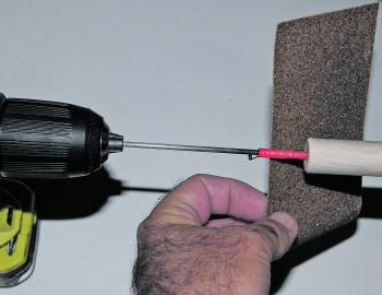 Put the top of the stem firmly into the chuck of your drill. Get the drill rotating and use your coarser sandpaper (50 grit) to begin rounding off both ends of the body. Do not push down hard enough with the sandpaper to flex the carbon stem or it may sna