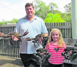 Scott McAuley and his daughter with some sizable mud crabs.