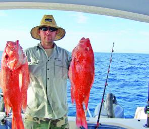 Ando holding up two beautiful red fish caught offshore.