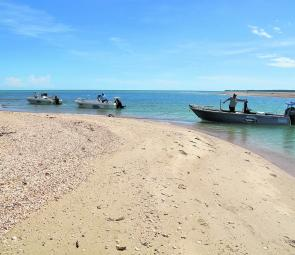 Sportsfishing boats lined up in a Cape York creek mouth waiting for the tide.