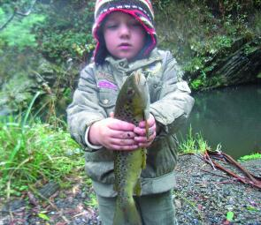 Young Lochie holds up an above average brown trout caught from a deeper section of stream.
