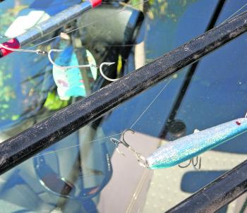 The tackle on your rods needs to be secured so that it doesn't come loose where it can fly around and damage someone. A large sinker could easily smash a windscreen, dent your vehicle or damage the blank of a rod if it came free. My advice would be to unr