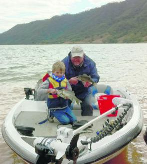 Peter Gogarty from Glenbawn Kiosk with his grandson Riley on a cold August day with his first bass in a comp.