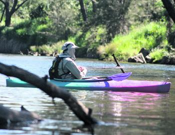 A sun smart kayak angler anticipates a bass surface strike.