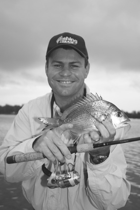 Why the silly grin? The author with the first fish caught on a new Design Rod made by Murray Allport.