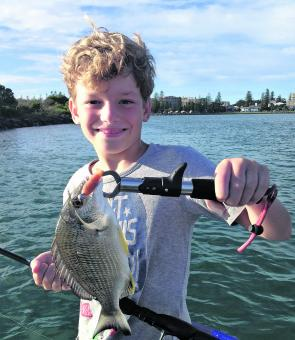 Young Bailey with his first fish on a lure. Pic courtesy of Castaway Estuary Charters.