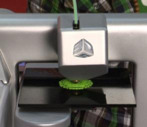Here you can see the printer head laying down the first support layers of green filament