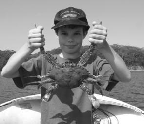 Young Jason Earl proudly displays one of the big blue swimmer crabs he and his Dad have been catching. There should still be time for the blueys and a mullet head is the top bait.