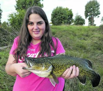 Hayley McDonald holds up a stocky Murray cod.
