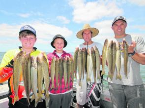 Some happy anglers with their arms full of tasty whiting.