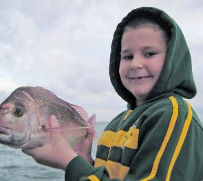 Keen young angler, Jordan, with his first bay snapper on a hard body.