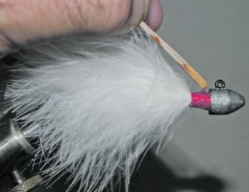 Continue to add similar amounts of marabou to the underside of the hook and the side closest to you until you have an even covering around the hook shank. Do repeated wraps of thread to secure and build up the area between the marabou and the jighead. Fin