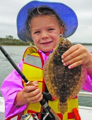 Calissa Badullovich, who loves using soft plastics, proudly displays one of the flounder she caught in a fishing competition.