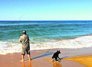 Belting a lure out into the surf. The dog's having fun chasing shadows, too!