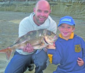 Jim Furlong and son Trav proudly display a top South Coast snapper captured from the rocks.