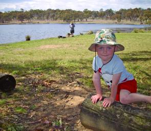 Young Louie Bakers enjoys the surrounds at Dumaresq Dam while a keen angler explores the shallows for a trout.