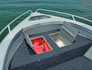There's a wide storage compartment under the front deck. Note the tie down handles for the owner's crab pots.