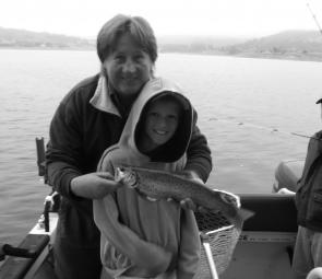 The author with Thomas Smith, 8, and a nice brown trout trolled up from the lake.