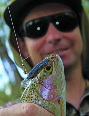 Sandy Hector of Wodonga admires a Yackandandah Creek rainbow trout he caught on a pontoon 21 Crackjack 48 lure last spring.