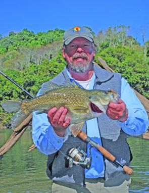 Steve Starling with a plump 47cm fork length bass pulled out of 5m of water on a soft plastic crept along the snaggy river bed.