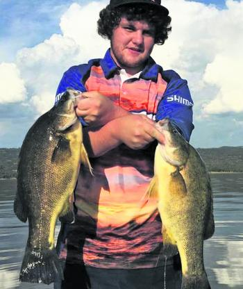 Brad Collison holding up two 50cm+ fish.