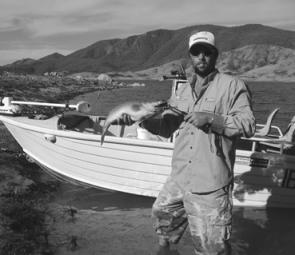 The author with an average cod from Blowering, caught off the rocky point in the background.