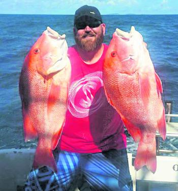 Tony Cox holds up two red emperor caught on a recent charter with Renegade.