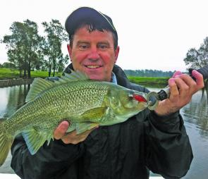 Mark Taylor with a 44cm river bass he caught on a River2Sea Baby Crank after a massive storm swept through.