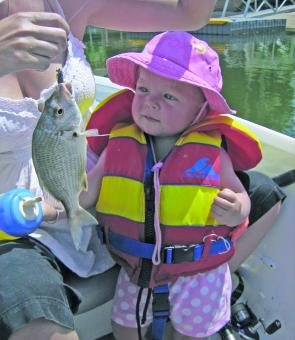Isla studies her big brothers fish –taking kids out fishing is great fun for the whole family.