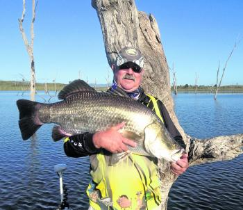Geoff Hodge with a fat 97cm barra he caught after the sudden rise in the lake.