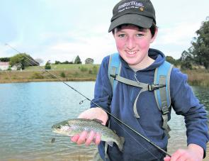 Will O'Connor with a yearling rainbow trout caught on a Strike Tiger Micro Spoon lure in Stanley Ditch Dam.