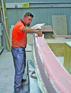 Darryn Burr applying filler (or 'bog') to the sides and gunwales to ensure a smooth and strong finish. As we didn't have the benefit of a moulded top to fit to the hull, this all has to be done by eye and hand – a very testing and often tedious job.