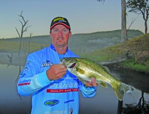 Tournament angler Wayne Beazley with a bass that smashed a surface lure just before sunrise. That's certainly a good time to try for bass on the top.
