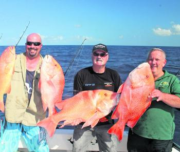 Happy customers holding possibly the tastiest pairing of fish – coral trout and red emperor.
