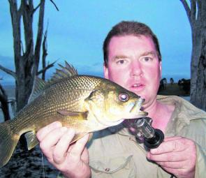 Craig Colley with a bass caught just on dark on a Megabass Siglett surface lure.