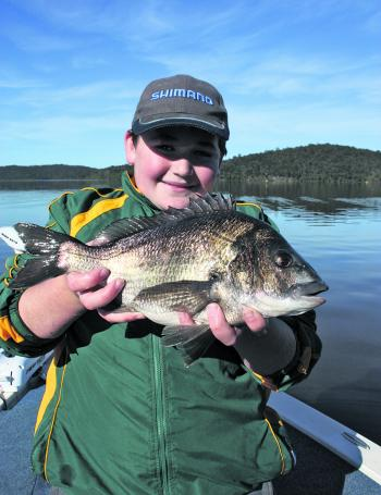 Tom Smith with a solid black bream he caught, which was released.