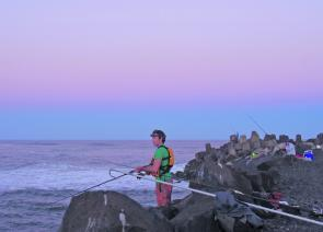 The South Wall at Ballina can get crowded when the mulloway are biting. Daniel Sloan patiently waits with a live tailor out at sunset.